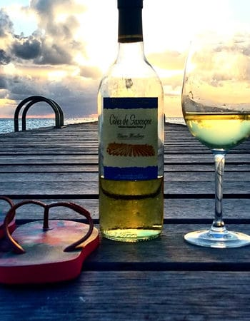Wine and sandals with a sunset in the background