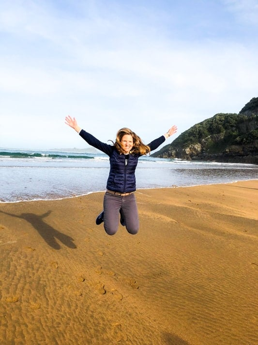 Expat Camilla jumping on the beach