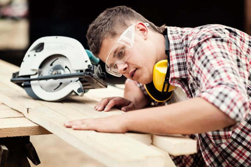 A skilled migrant woodworker cutting wood