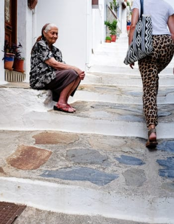 Old lady sitting on stairs in Greece