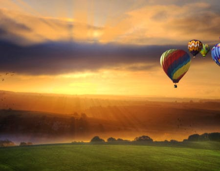 Stunning sunrise of hot air balloons over South Downs landscape