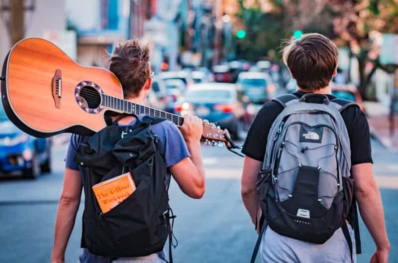 two travellers on a working holiday visa with a guitar and backpack