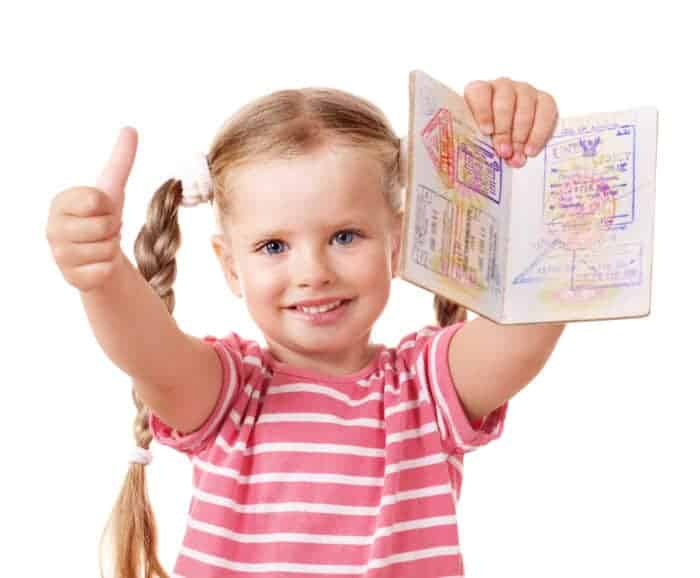 Girl holding up her passport that she inherited from her parents