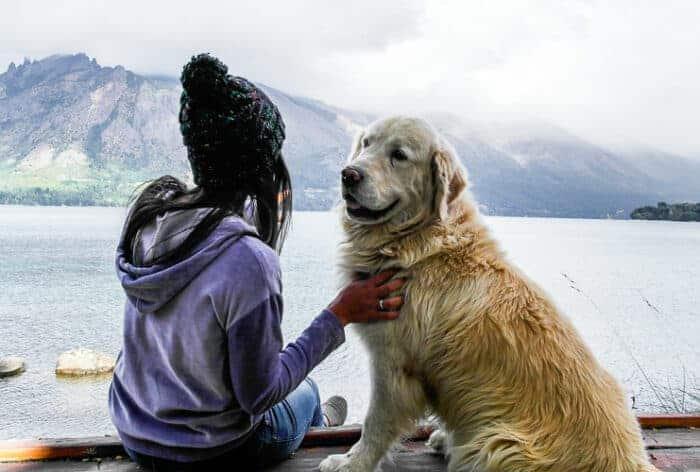 A student and her dog next to a lake in Argentina.