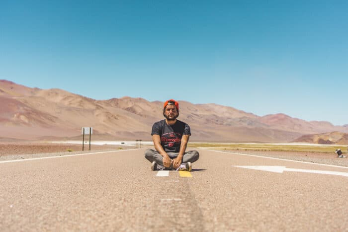Argentinian citizen by descent in the middle of the road with mountains behind him