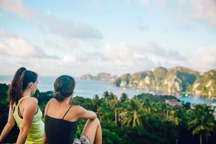 Two girls looking over the ocean in Thailand, one of the cheapest places to live in Asia.