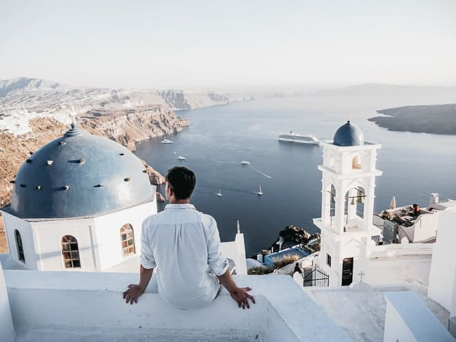 A man looking over Santorini in Greece where you can get residency.