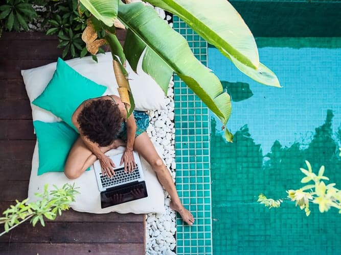A women working remotely next to a pool