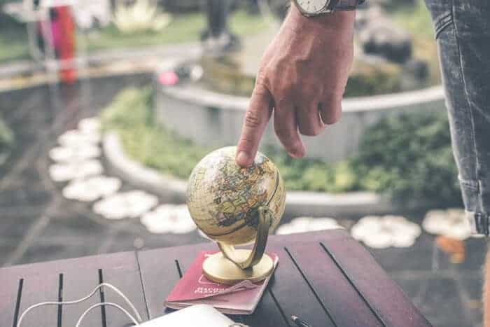 Man pointing at a globe thinking about where he can get residency.