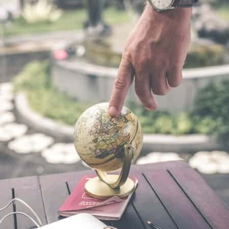Man looking at a globe to decide on residency