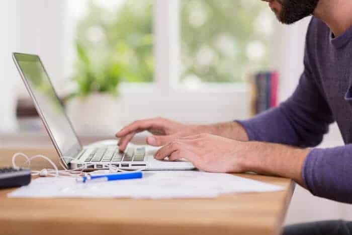 A man on his laptop making an international money transfer