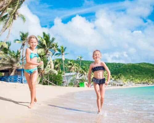 Two grils running on a beach in Barbados