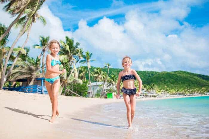 Two girls running on a beach in Barbados