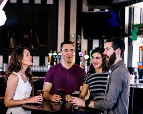 Friends enjoying living in Ireland having a pint in an Irish pub