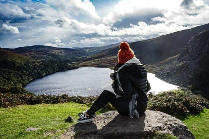 A girl in Ireland who has a resdency visa overlooking a lake.