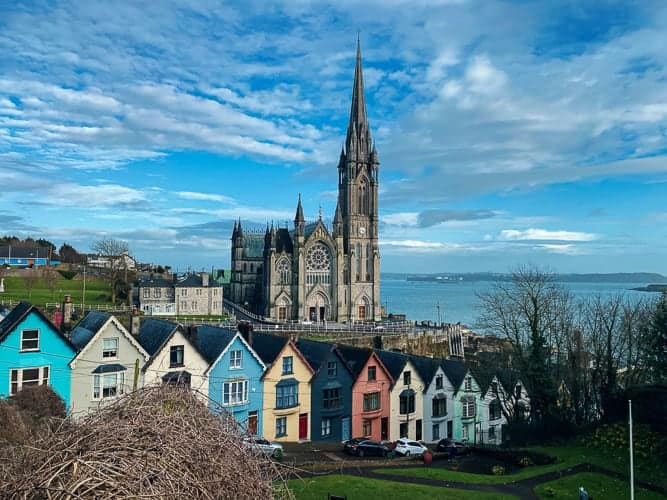 A cute village in Ireland with coloured houses and a church in the background.