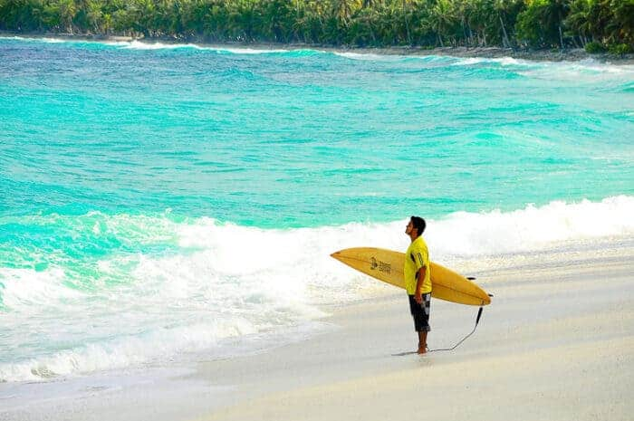 A surfer in the Carribean in Barbados on a Welcome Stamp Visa