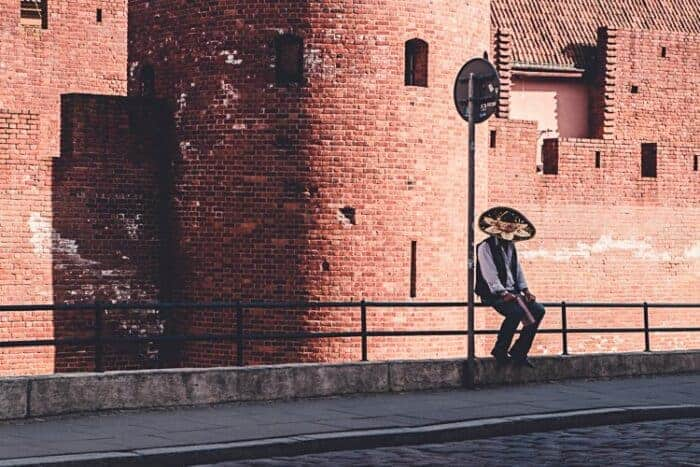 A man in a Mexican hat in front of a beautiful building